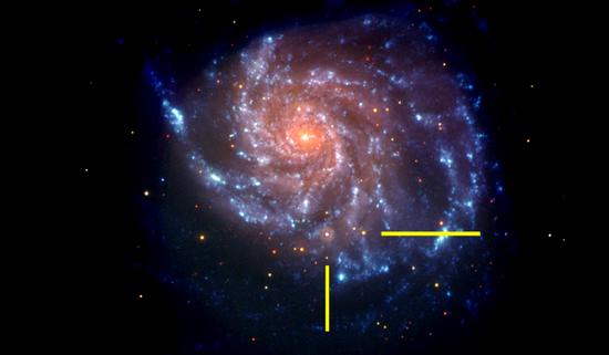 可见光和紫外线下,Swift卫星拍摄的M101星系照片,黄色线代表超新星SN2011fe的位置。照片是伪彩色的,蓝色表示紫外线部分,红色表示可见光部分。