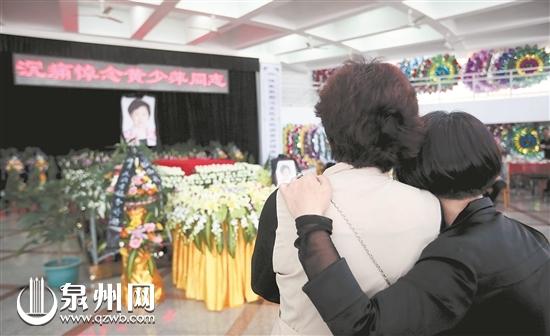 悼念大厅,两位前来吊唁的女士沉浸在悲痛中。