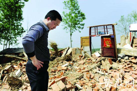 风灾中去世老人的侄子站在叔叔家的废墟上,仍无法接受这个事实。