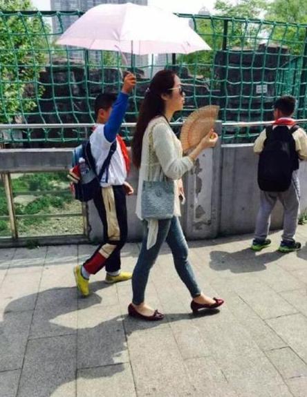图为网友爆料的照片中,小学生为一名女子打伞。