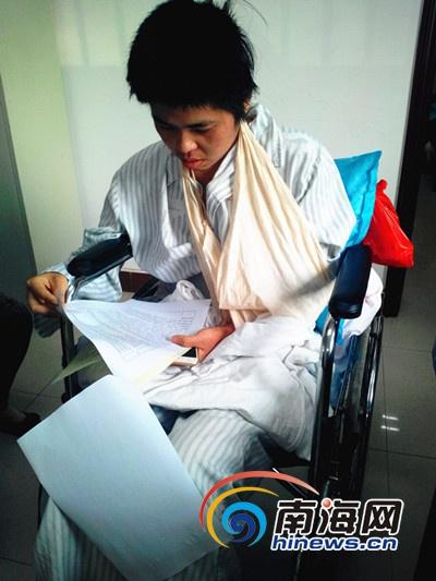 伤者张某坐在轮椅上阅看《交通事故责任认定书》 (南海网记者 刘培远 摄)