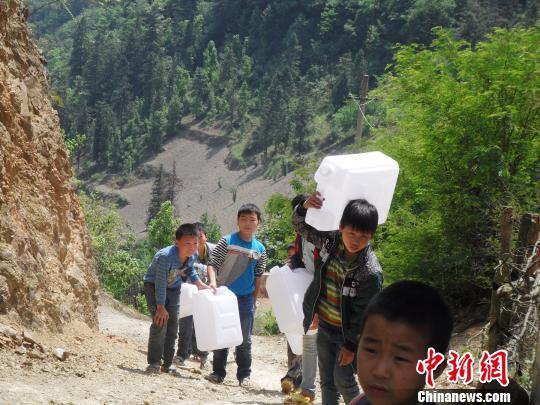 每天长途跋涉取水小学生们。滕树维摄