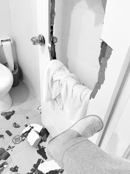祝先生虽然把厕所门凿个洞,但脚因此受伤。半岛晨报、海力网见习摄影记者刘美行