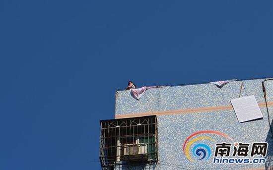 一名女子站在楼顶要跳楼。