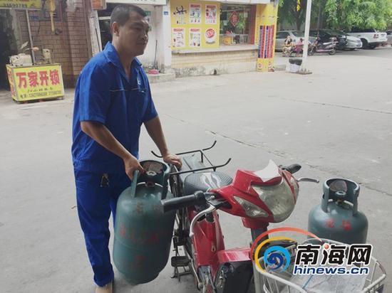 燃气公司的工作人员用电动车送煤气罐(南海网记者 陈望 摄)