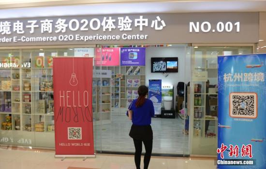 资料图:4月22日,市民在杭州首家跨境贸易O2O体验中心里扫码购物。中新社发 李晨韵 摄