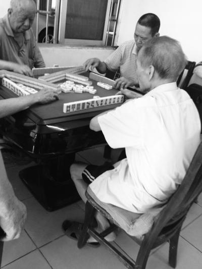 老人在小区活动中心打麻将