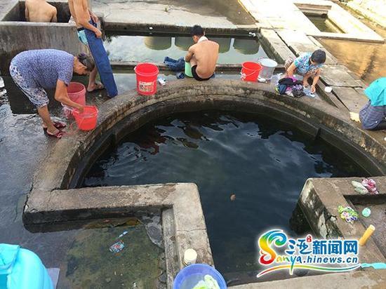 5月13日,人们在三亚崖州古迹之一的既济亭热水池洗澡、洗衣服。(三亚新闻网记者 沙晓峰 摄)