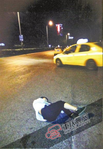 江开国保护的男子躺在马路中间不省人事,一动不动。重庆晨报记者 雷键 摄