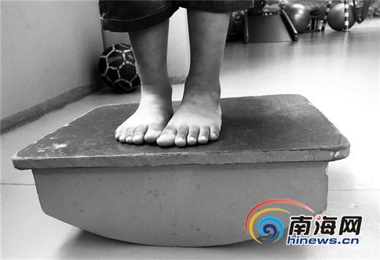 一名孤独症患儿站在平衡台上,练习平衡感。