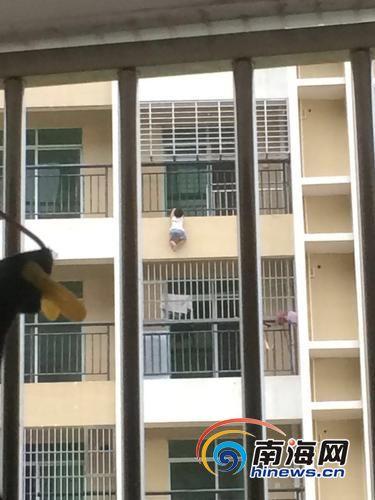 男孩钻出防护栏,悬挂在空中。(市民供图)