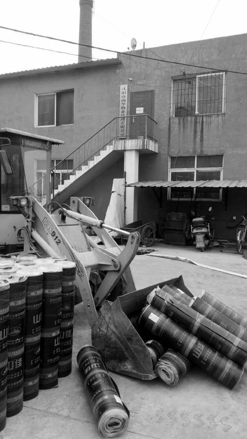 业用铲车将防水用的油毡纸卷运到居民楼下。