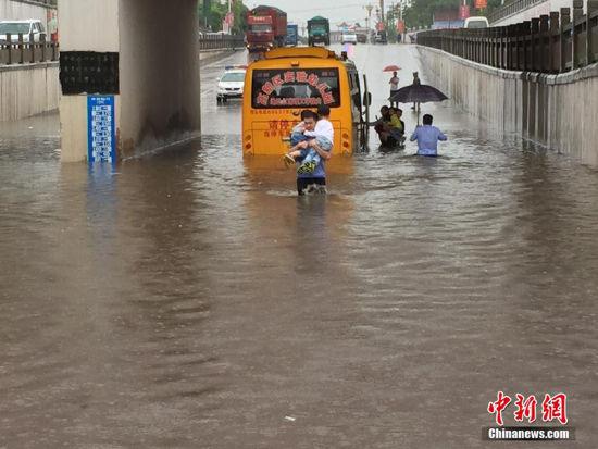 江西突降暴雨校车被困,交警涉水转移29名幼儿。