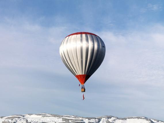 艺术家挑战在腾空的热气球下面倒立。