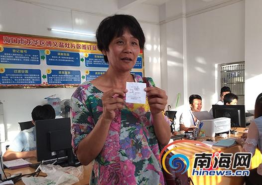 市民陈爱兰拿到首个登记编号,她兴奋地告诉记者,从19日上午就来排队了,尽管过程辛苦,但是为了能优先签协议和选房也值了。(南海网记者 陈丽娜 摄)