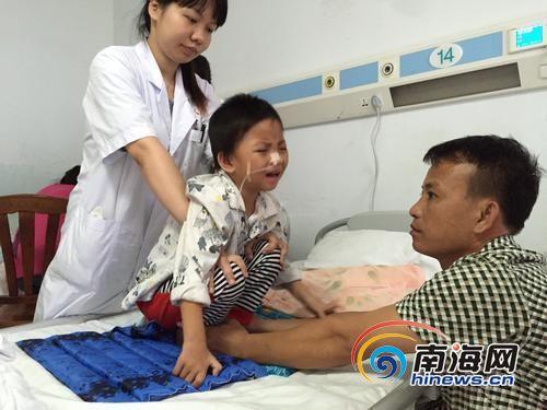 护士在给无意识中的小婷做肢体康复训练,父亲在一旁帮忙。