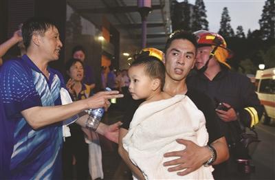 消防队员抱着被困小男孩一口气跑下44楼。