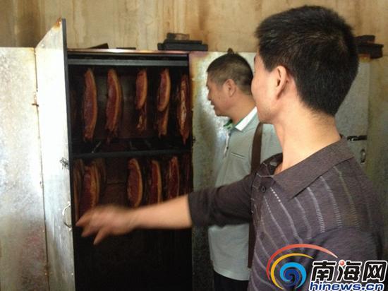 执法人员检查小作坊主刘弘熏肉生产过程。