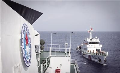 5月25日,在中沙海域神狐暗沙,三沙市综合执法1号船执法人员举行了庄严的升国旗仪式。