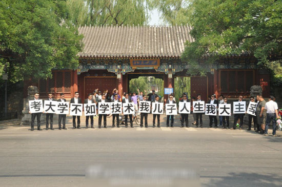 一群黑西服、黑墨镜的男子突然出现在北京大学校门前,抗议高考。