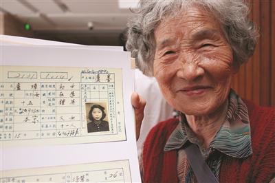 徐璋老太太与户籍卡上70年前的自己。 张可 摄