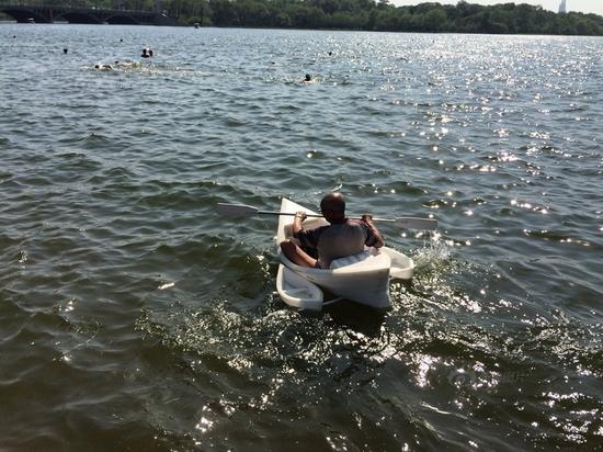 图为老人在南湖划着自制游船。
