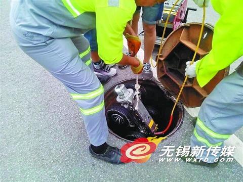 市政养护工人将检测机器人放入井内,准备工作。