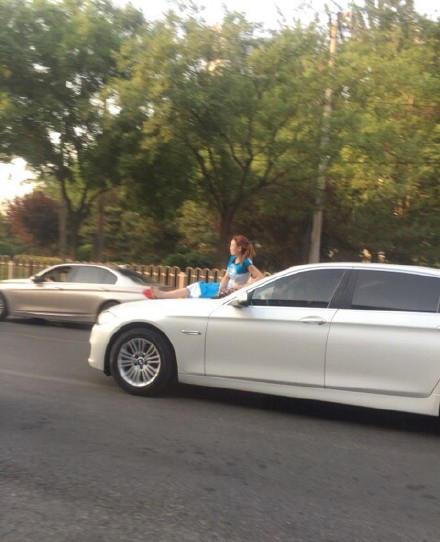 女子坐在轿车引擎盖上行驶而过 惊呆网友 图图片