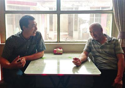 昨日午饭后,李万良和王瑞全父子坐在客厅唠嗑。新京报记者 李相蓉 摄