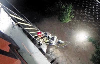 消防员搭起绳梯下崖救人。