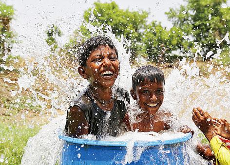 在印度艾哈迈达巴德郊区,男孩们在塑料桶中玩水避暑。新华社发