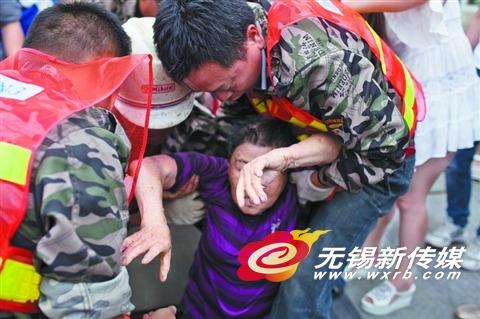 施工工人和过路市民一起将坠井老人营救出来。 (邹国清 摄)