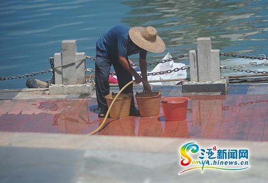 6月4日,三亚市民在路边接水。(三亚新闻网记者沙晓峰摄)