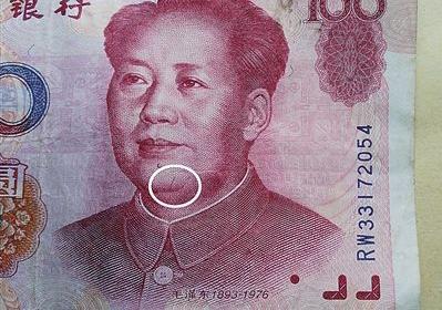 99年版百元大钞头像右边痣下方,有一条3毫米的红色竖曲线(白圈处)。