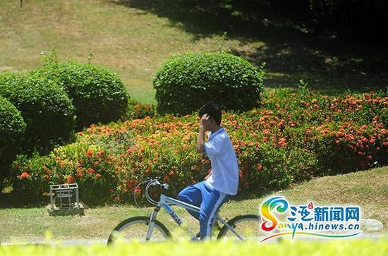 6月4日,一学生双手不扶车龙头骑行在三亚凤凰路上。(三亚新闻网记者沙晓峰摄)