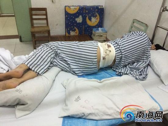 韦智贵侧卧在病床上,背部的刀伤让他无法平躺。