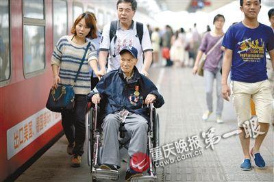 102岁抗战老兵曹廷明坐轮椅,在志愿者的搀扶下踏上回家之路。