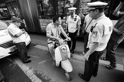 今晨,民警在南三环主路对违反上路的摩托车进行查处  摄/法制晚报记者 杨益