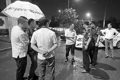 昨晚,警方对查获的黑车司机(左四)进行罚款   摄/法制晚报记者 柴程
