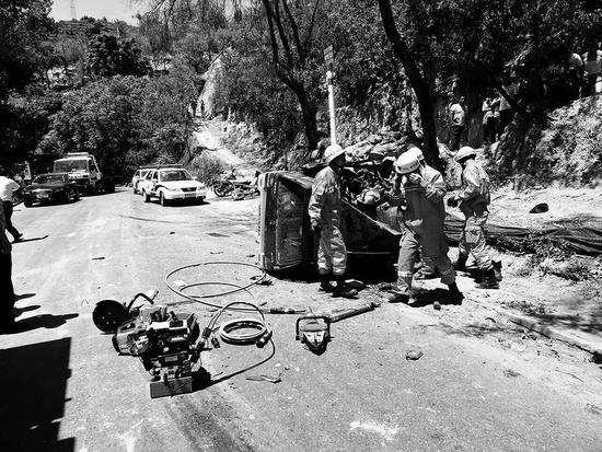 消防人员正在使用切割工具对事故车进行破拆