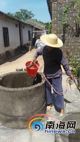 定安年过八旬的陈阿婆正在打水。