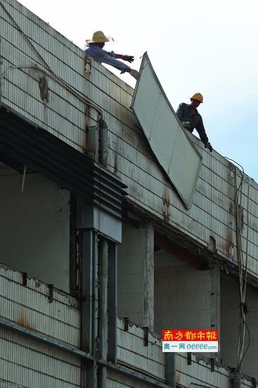 工人正在拆除检查站大楼外墙的装饰板。