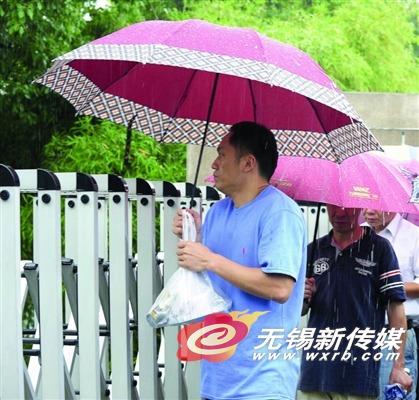 昨天中午,一位买好快餐的家长在大雨中等候中考的孩子。
