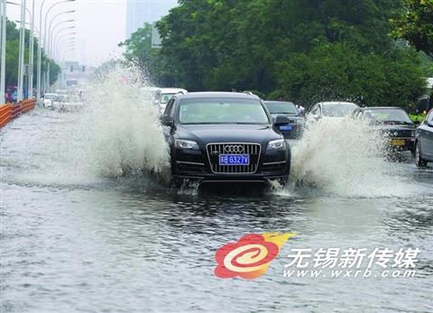 昨天,车辆经过惠山大道积水路面。(还月亮 摄)
