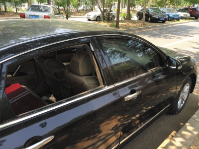一辆黑色轿车的右后侧车窗玻璃(画圈处)被砸碎。