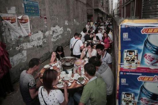 玉林当地人在街上吃狗肉。(图片来源:《镜报》)
