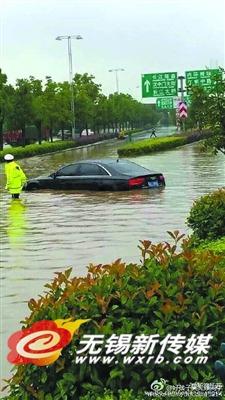 道路积水严重,小轿车已淹道路中央。