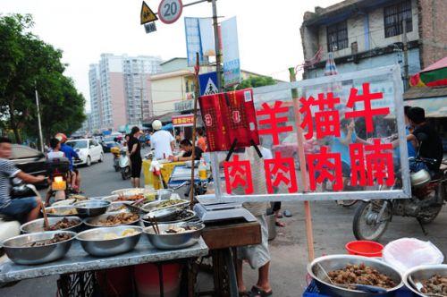"""资料图片:玉林市区南桥市场的一家卖肉摊把招牌中的""""狗""""字遮住。新华社发"""