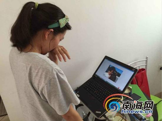 刘某看着自己和崔某的亲密相片流泪(南海网记者组摄)
