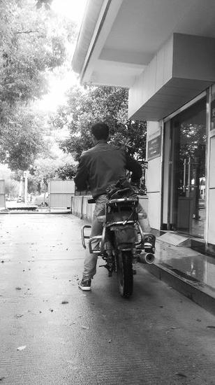鲁某骑摩托车在检察院门口询问妻子判决情况。 记者谭在龙 摄
